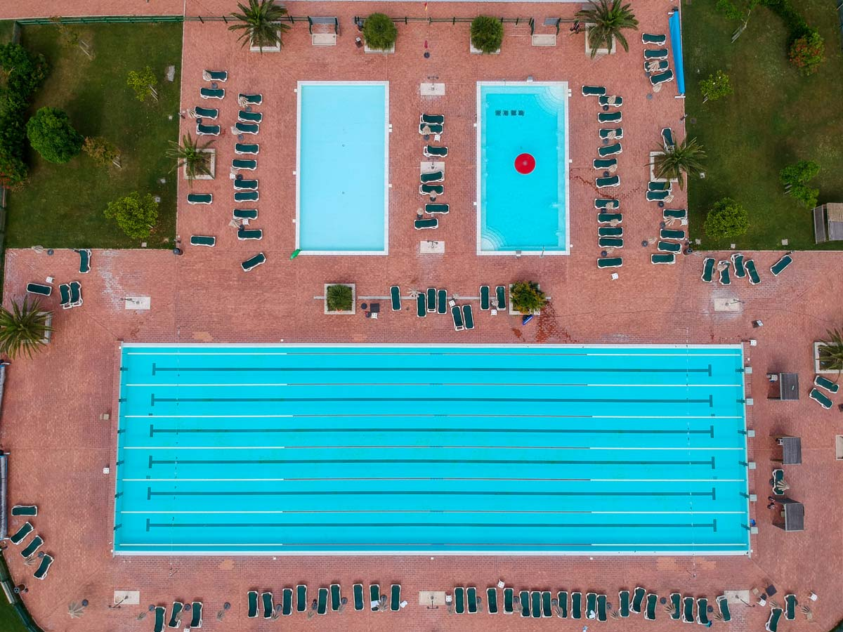 top down view of swimming pools with poolside sun loungers