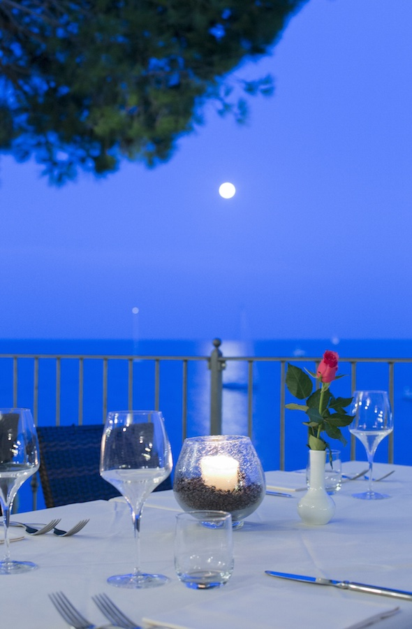Laid table on a balcony with the sea, night sky and moon in the background