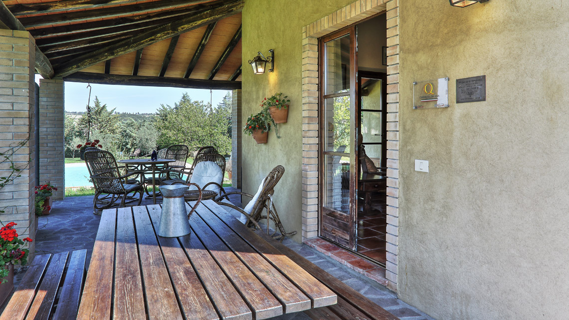 outside shaded porch with table and chairs Le Selvole Farmhouse