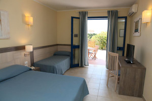 Room with a double bed, a single bed, TV, desk, chair and balcony