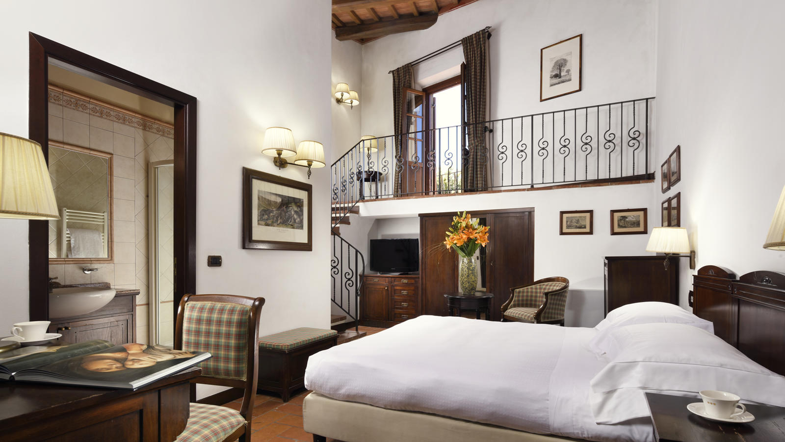 bedroom with double bed and indoor balcony Unahotels Palazzo Mannaioni Toscana