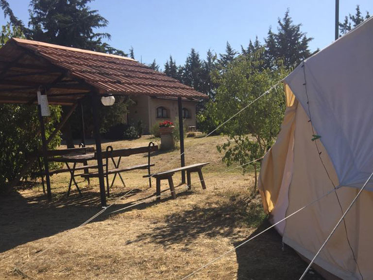 white tent next to a shelter Le Selvole Farmhouse