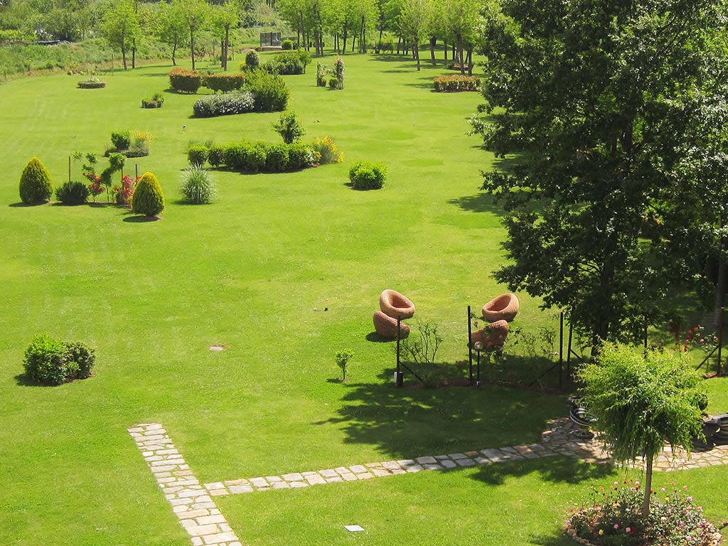 grass gardens with trees and seating Hotel Certaldo