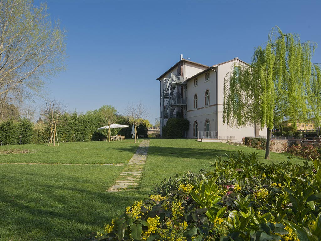 grassed gardens with trees and the hotel building Hotel Certaldo