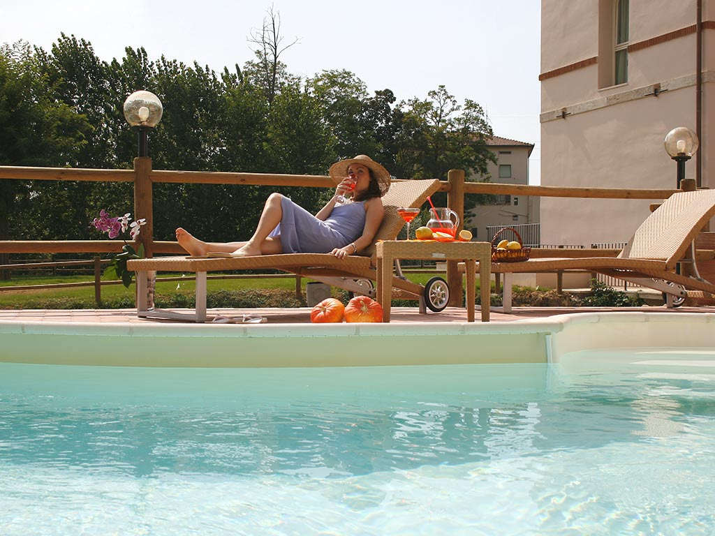 woman on sun lounger by the swimming pool Hotel Certaldo