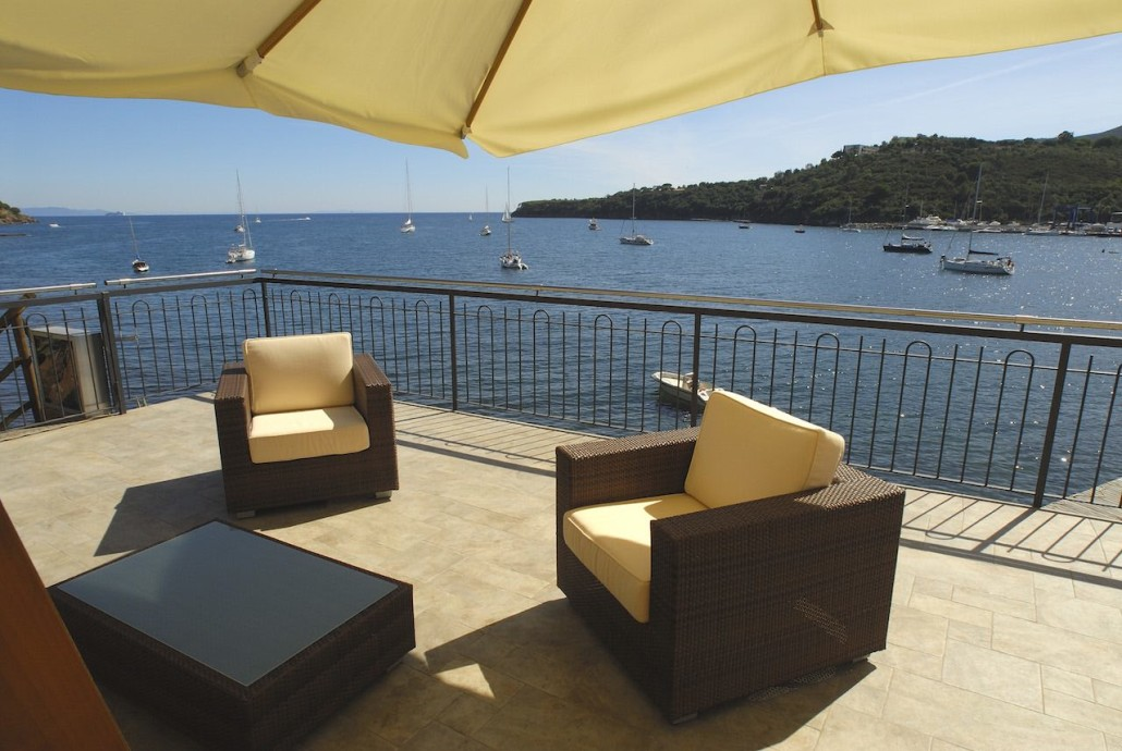 Outdoor shaded lounge area with seating and a view of the harbour
