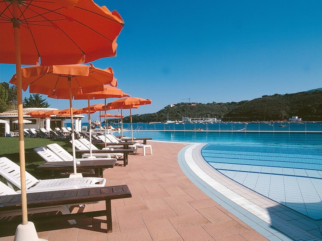 Swimming pool with poolside sun loungers, umbrellas and a view of the sea