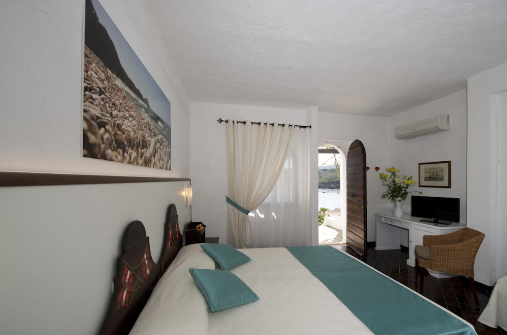 Room with king size bed, TV, sofa and terrace