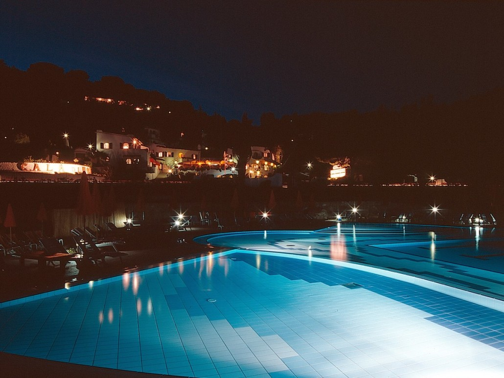 Swimming pool at night with the hotel in the background