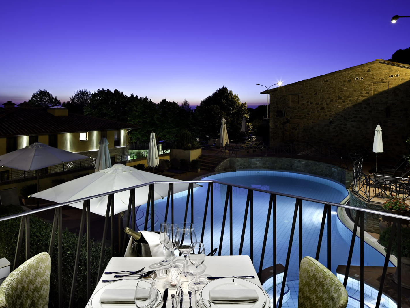 dining table on balcony overlooking swimming pool at night Unahotels Palazzo Mannaioni Toscana