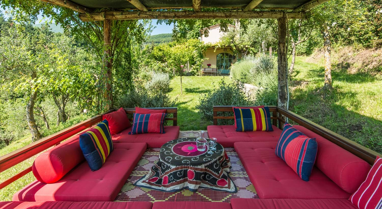 garden sofas and table under shaded patio surrounded by grass Villa La Torretta