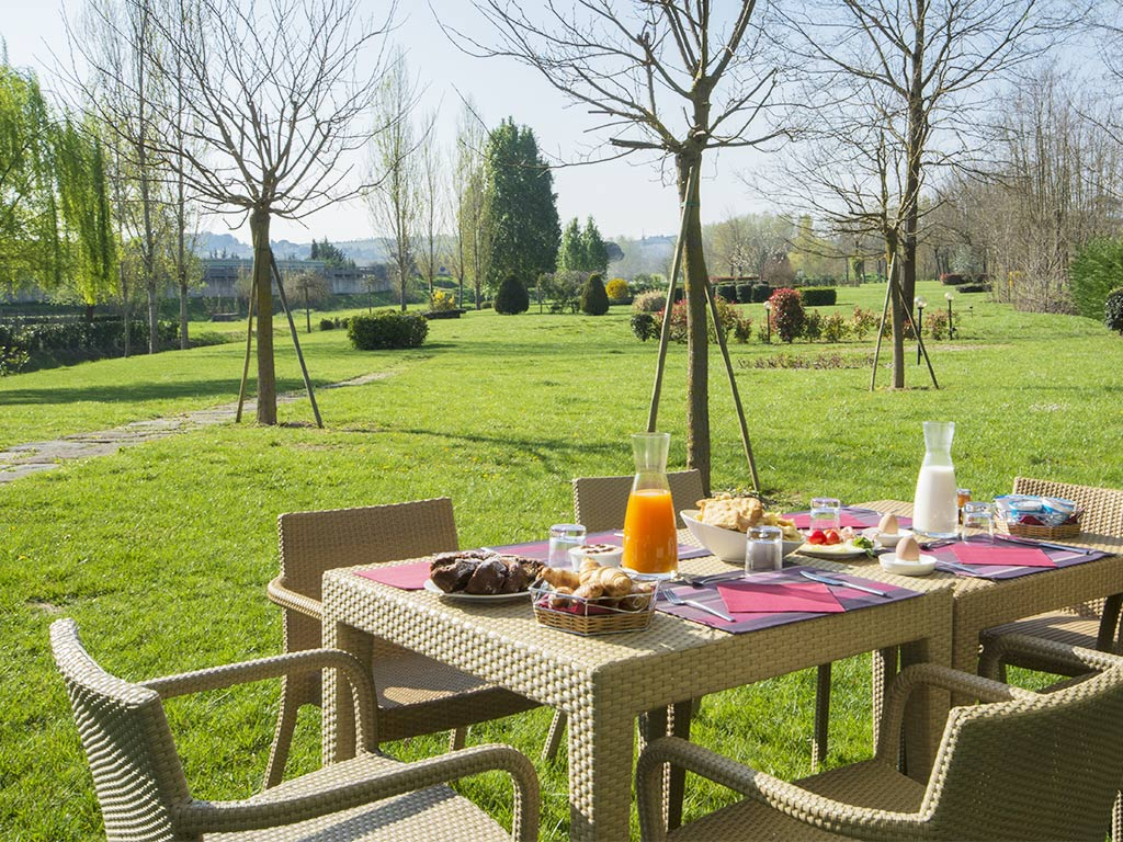 outside dining table and chairs with breakfast foods Hotel Certaldo