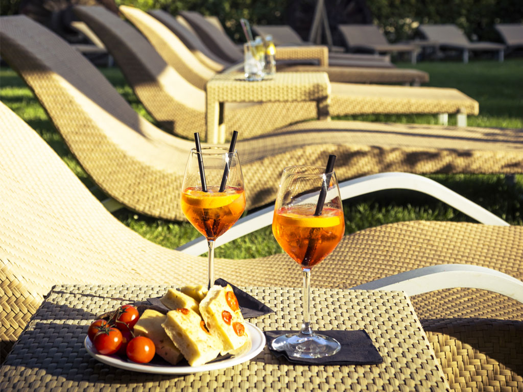 sun loungers with tables, drinks and cake Hotel Certaldo