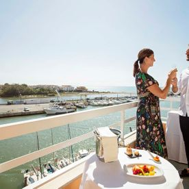 couple having a drink on a balcony overlooking the bay