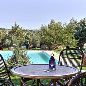 outside table and chairs in garden with swimming pool Le Selvole Farmhouse