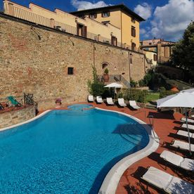 swimming pool with sun loungers beside it Unahotels Palazzo Mannaioni Toscana