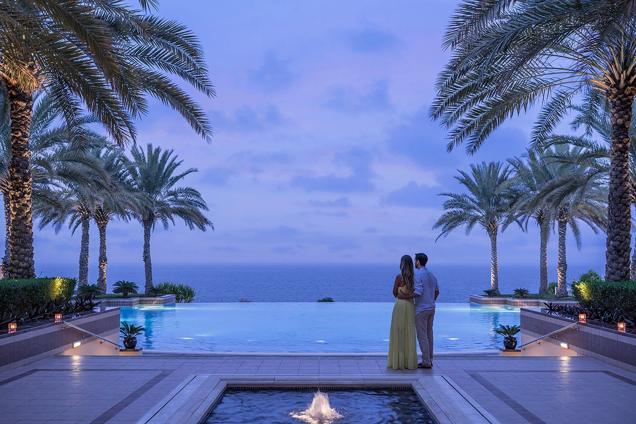 Couple looking out across the swimming pool and sea at sunset