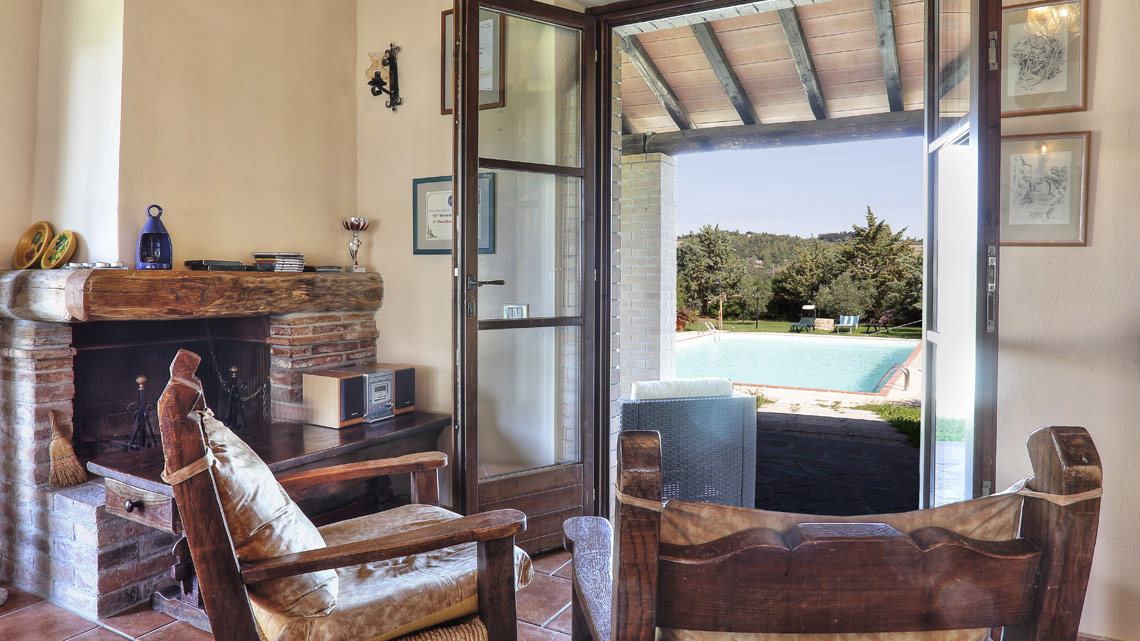 lounge with french doors opened out to porch and swimming pool Le Selvole Farmhouse