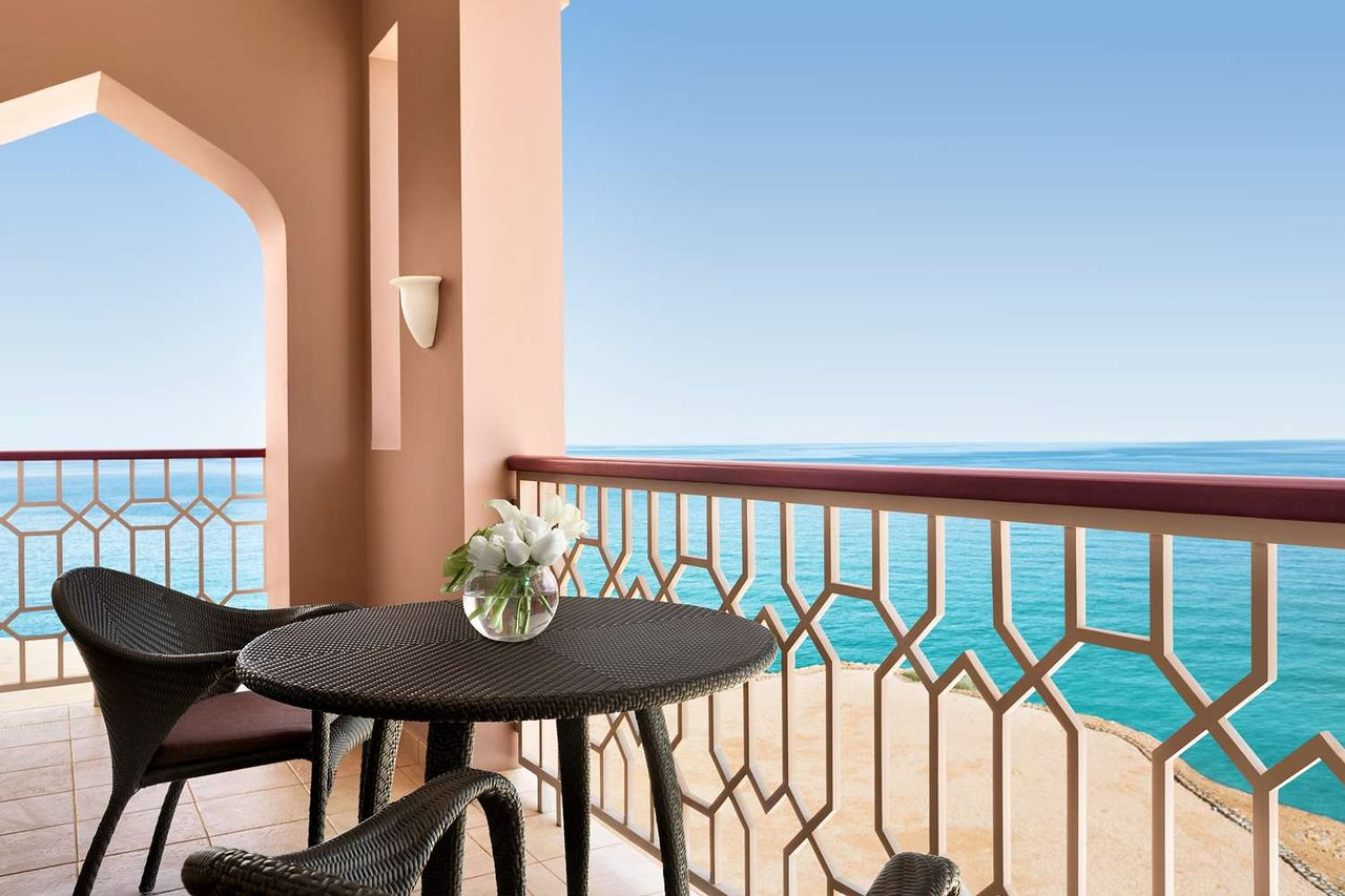 Table and chairs on a balcony with a view of the sea