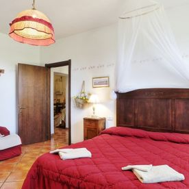 bedroom with double bed and sofa Le Selvole Farmhouse