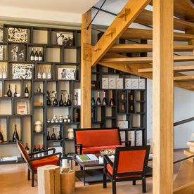 room with coffee table, chairs, shelving unit with wines and wooden stairs