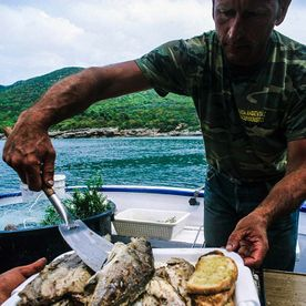 man serving cooked fish on a boat